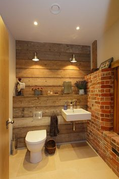 Rustic bathroom with reclaimed wood and exposed brick walls [Design: Hampshire Light]