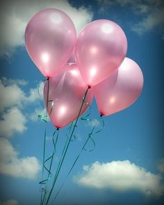 pink balloons against cloudy blue sky