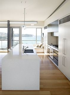 White Caesarstone countertops overlook a beautiful ocean view. White Caesarstone countertops overlook a beautiful ocean view. Corner Kitchen Layout, Sleek Kitchen, Open Plan Kitchen, Caesarstone Kitchen, Ceasarstone Countertops, Kitchen Benches, Home Kitchens, Kitchen Renovation, Kitchen Design