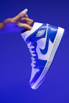 """Jordan Brand goes old school on the Women's Air Jordan 1 Mid """"Kentucky Blue."""" Equipped with a white leather base and blue leather panels and Swoosh branding, the women's shoe replicates the color block of the Nike Dunk's original """"Kentucky"""" colorway."""