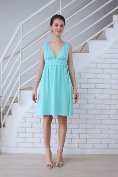 Robe cocktail. La robe de soirée vert mint Anémone est sans manche. Elle à un large décolleté en forme de v devant. La taille est ornée d'une ceinture à plis religieux et la jupe est froncée.