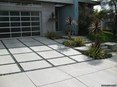 The driveway looks magnificent with the concrete tiles and gravel in between. Tope colors and palm trees go very well with the modern touches.
