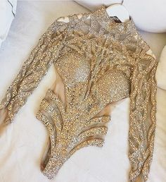 I'd say this costume is totally set to take the stage! In all of its sparkling glory this #custom bodysuit creation is absolutely breath taking! The gold embellishments and sparkling embroidery is rich in detail the gems strategically cover just the rite areas creating intricate patterns and shapes. A nude sheer chiffon fabric creates a reviling but tasteful nude allusion!
