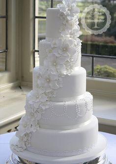 Torta de boda de color blanco decorada con flores de azúcar en cascadas y cadenas de perlas.