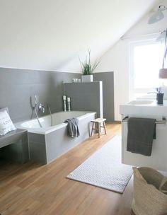Badezimmer mit Holzboden und grauen Fliesen.