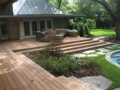"I am noticing a trend in deck design...wide expanses of steps ( I like ) and NO railings. I'm not sure about the no railing. Also, the stepping stones look like broken up concrete from the ""before"" phase."