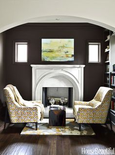 In the library alcove, walls and trim painted a rich gray-brown, Sherwin-Williams's Griffin, recede into the background to highlight the mantel by FranÇois & Co. CR Laine's Hans chairs in Lewis & Sheron Textiles' Pandros. Organic Modern rug, Surya.