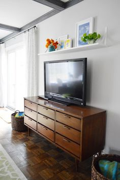 Living room -- dress up the space above the tv...  from: Young House Love