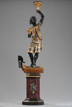 A late 18th century gilt and polychrome wood candle holders depicting a Nubian standing up and holding a torch, resting on the front part of a gondola with its metal bow, above a plinth painted in imitation of porphyry. Venetian work. Light wear to the patina.  Circa :1790
