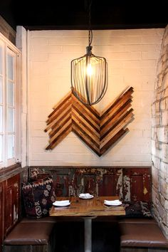 The wood paneling running along the bottom of the wall is built from old doors found in Brooklyn. The large light fixture is a thirty pound industrial whisk from an antique dough mixer.