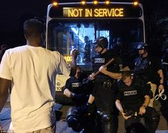 A man points at police officers wearing riot gear, standing in front of a bus…