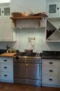 Opalescent kitchen white cabinets black granite for Solid glass backsplash behind stove
