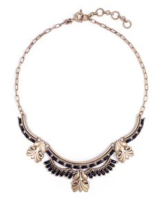 Ornate filigree and rich onyx-colored stones create a harmonious display on this collar necklace.