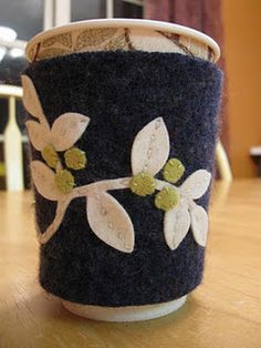 Wool felt coffee cozy with white vine and berries.