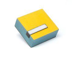 """Julia Turner """"Yellow Block Brooch"""", 2012. Wood, steel, vitreous enamel. 1 x 1 x .5 in (2.5 x 2.5 x 1.3 cm)."""
