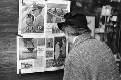 In Berlin, a German woman reads a copy of the Berliner Illustrierte newspaper, featuring photographs of Mussolini's official visit to Berlin in September 1937.