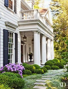 Boxwood hedges and stone steps to the front door perfectly frame this classically elegant home's exterior.