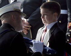 El niño de ocho años de edad, Christian Golczynski acepta la bandera por su padre, quien fue miembro de la Marina, el Sargento Marc Golczynski, durante un servicio conmemorativo. Marc Golczynski recibió un disparo en una ronda durante su segunda misión en Irak (para la cual se había ofrecido como voluntario) tan sólo unas semanas antes de la fecha en que debía volver a casa.