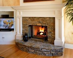 Stone Fireplace White Mantel...kind of what I'm thinking, without the big semi-circle hearth.  With the brick dust red color behind the fireplace with the metal light on each side!