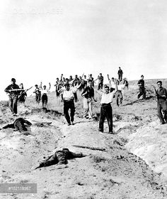 Photograph showing a group of Republican Government troops surrendering to the Nationalist army on the Guadarrama Front during the early stages of the Spanish Civil War, 1936. In the foreground are two dead Nationalist soldiers.