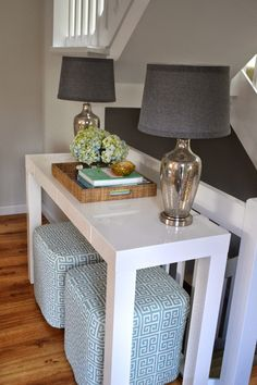 Living space designed by Summerland Homes and Gardens. A white parsons console table from West Elm located near the front entry provides a stylish space to drop keys and mail. Greek key ottoman cubes can be pulled out for extra seating in the living room when needed.