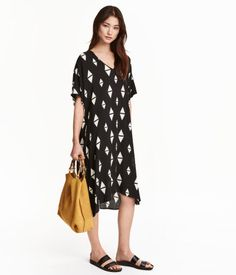 Calf-length dress in woven viscose fabric with a printed pattern. V-neck, short, wide sleeves, and slits at sides. Slightly longer at back. Unlined.