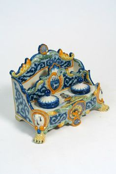 HR QUIMPER FRENCH POTTERY DOUBLE INKWELL DESK SET. The letter rack separated from covered twin inkwells, the whole footed, having shell crest and base front, hand painted with coastal scene; man playing bagpipe seated on rock. Marked on top, HR Quimper and again on back. Height 6 1/2 in., width 8 3/4 in. c. 1920's