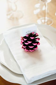 Sometimes, the most fitting decor can be found in your own backyard — and these pinecones get even more festive with an unexpected pop of color. Click through to get the tutorial and see more easy DIY Thanksgiving place cards! #thanksgivingplacecardsdiy #thanksgivingplacecardideas #easythanksgivingplacecards #thanksgivingplaceholdersdiy