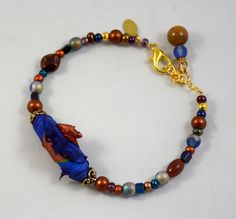 My handmade tyvek bead is surrounded by various glass beads to complete this bracelet. Beadwork by cgm