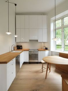 L-Shsped kitchen, white cabinets, butcher block countertops, wood kidney shaped dining table, Dinesen Heart Oak Floor | Remodelista
