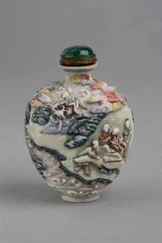 [Snuff bottle] Porcelain, moulded in relief and painted  [Stopper] Coloured glass set in metal