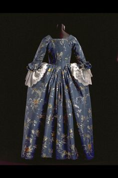 Rear view, robe à l'anglaise, c. 1765. Dark blue silk taffeta brocaded with flowers in pink, yellow, grey an dbrown.