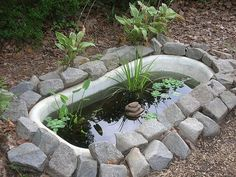 "Interesting little pond -- and excellent recycling! I suspect if you had a tub with a faucet fixture, a handy person could turn it into a ""waterfall"" of sorts."