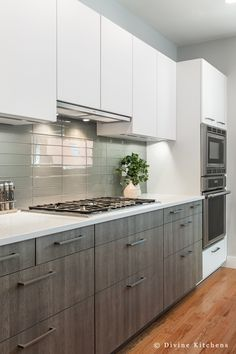Built in hood. gray base cabinets. oven microwave . glass backsplash. divinedesignbuild.com