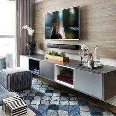 """""""Sala de tv com rack suspenso,tons de cinza que casam com o tapete azul e painel amadeirado!! """""""