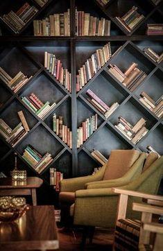 unique bookshelf design, black wall of bookshelves, pantone warm sand, light beige, light tan, tan accents in dark room