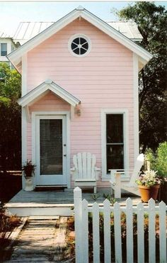 Adorable mini pink house with white picket fence