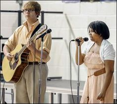 Faith Dickerson, 15, accompanied by Ross Thompson of the Toledo School for the Arts, sings 'School Is A Good Thing,' an original composition she wrote, during her class graduation on Tuesday.  (Toledo Blade, June 2014)