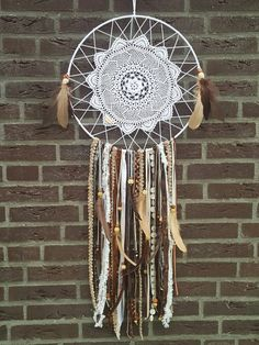 I made a big Dream Catcher for our own bedroom. I used a vintage doily, cotton yarn, feathers en a lot of ribbons in all kinds of sorts and some wooden beads.