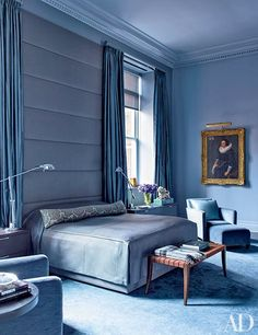 The periwinkle upholstered headboard, curtains, and carpeting lend a cozy and peaceful air to the master bedroom of a Manhattan apartment devised by Bruce Bierman; the 17th-century portrait is by Willem van der Vliet.