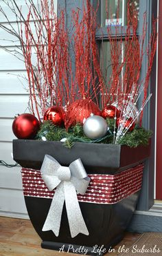 Use a big flower pots as a base, and fill them with evergreen garland,   huge ornaments, sparkly twigs and white lights!  A package full of sparkle!  They look very pretty all lit up at night too!