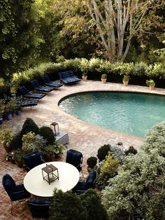 Interesting concept -- oval pool in a squared terrace with gardens surrounding. Like the pool's bottom color too.