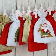 """All-Inclusive Adventskalender """"Weiße Weihnacht"""".  Weihnachtliche Stickereien auf weißem Stoff umrahmt von sattem Rot und schimmerndem Gold."""