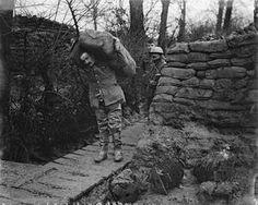 WWI, Jan 1917; Lancashire Fusilier wearing waders taking a load of sandbags up a communication trench, Ploegsteert Wood. ©IWM