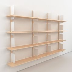 HS1 shelving system: a unique bracket combines two important functions - shelf support and bookend. The brackets can be wall mounted or on wooden rails and are available in white, black, blue, or yellow. Combined with wooden planks a refreshingly functional shelving system is born.