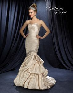 Sublime satin bridal gown with pleated torso and sparkling oblique band of beads, sequins and rhinestones at the bottom separating skirt of gathered satin fabric. There is a sweetheart neckline and chapel train. Available in a size 10. Priced at $799.00. (Store Style #W0786)