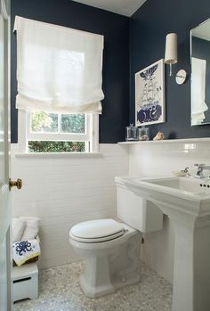 White and navy cottage bathroom features upper walls painted navy and lower walls clad in white subway tiles lined with a pedestal sink and a polished nickel mirror illuminated by Ziyi Sconces.