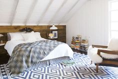 In place of a headboard, this owners of this Pennsylvania  home covered the wall behind the bed in oak rescued from a Pittsburgh bank. An outlet-store dhurrie rug softens the bedroom floor, while an Ethiopian cotton throw drapes the Restoration Hardware quilt.   - CountryLiving.com