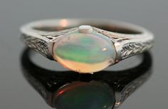 This ring has an oval opal set sideways in a delicate white gold mounting. The oval has a lot of fire and the setting has an intricate pattern which continues around the band.