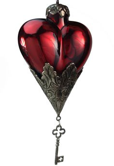 Adorne your tree with this beautiful glass heart ornament with metal key embellishment. - Designed by Eric Cortina. - Glass and metal ornament. - Makes a beautiful gift for a loved one. - Imported.